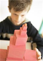 Child behind stack of blocks, focus on foreground Stock Photo - Premium Royalty-Freenull, Code: 695-05776443