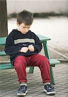 sad child sitting - Child sitting on bench Stock Photo - Premium Royalty-Freenull, Code: 695-05776468