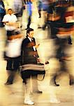 Businessman in blurred crowd, using cell phone, full length Stock Photo - Premium Royalty-Freenull, Code: 695-05776523