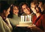 Woman holding birthday cake in group Stock Photo - Premium Royalty-Free, Artist: Cultura RM, Code: 695-05776641