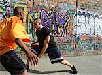 Man dribbling basketball, opponent blocking, next to graffitied wall Stock Photo - Premium Royalty-Free, Artist: CulturaRM, Code: 695-05776785