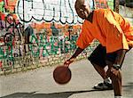 Man dribbling basketball next to graffitied wall, close-up Stock Photo - Premium Royalty-Free, Artist: Ikon Images, Code: 695-05776788