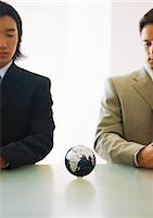Two businessmen looking down at small globe on table Stock Photo - Premium Royalty-Freenull, Code: 695-05776897