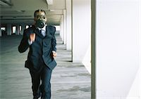 people in panic - Businessman running with gas mask covering face Stock Photo - Premium Royalty-Freenull, Code: 695-05776909