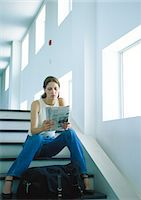 Woman sitting on stairs, reading newspaper, full length Stock Photo - Premium Royalty-Freenull, Code: 695-05776941