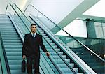 Businessman riding down escalator Stock Photo - Premium Royalty-Freenull, Code: 695-05776953