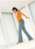 Woman walking on back of sofa, low angle view Stock Photo - Premium Royalty-Freenull, Code: 695-05777022