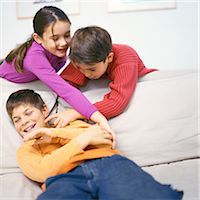 Boy and girl leaning over sofa, tickling second boy on sofa Stock Photo - Premium Royalty-Freenull, Code: 695-05777047