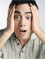 people in panic - Man looking at camera with eyes wide open and eyebrows raised, holding face with hands Stock Photo - Premium Royalty-Freenull, Code: 695-05777279
