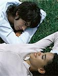 Young man lying on stomach and young woman lying on back on grass, head and shoulders Stock Photo - Premium Royalty-Free, Artist: ableimages, Code: 695-05777331