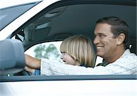 Man driving car with son on lap, side view Stock Photo - Premium Royalty-Freenull, Code: 695-05777424