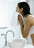 Woman standing over sink drying face with towel Stock Photo - Premium Royalty-Freenull, Code: 695-05777445