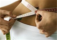 Woman measuring waist, close-up Stock Photo - Premium Royalty-Freenull, Code: 695-05777483