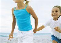 Two little girls, hand in hand on beach Stock Photo - Premium Royalty-Freenull, Code: 695-05777921