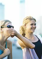 Two teenage girls, one covering the other's mouth Stock Photo - Premium Royalty-Freenull, Code: 695-05778003