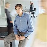 Man sitting on edge of desk in busy office Stock Photo - Premium Royalty-Free, Artist: Glowimages               , Code: 695-05778267