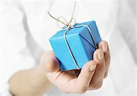 present wrapped close up - Hand holding out small package Stock Photo - Premium Royalty-Freenull, Code: 695-05778718