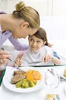 Girl sitting in hospital bed smiling up at mother while eating meal Stock Photo - Premium Royalty-Freenull, Code: 695-05779166