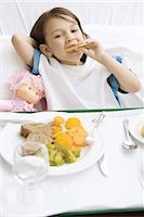 Girl lying in hospital bed with food tray in front of her, eating cookie Stock Photo - Premium Royalty-Freenull, Code: 695-05779167