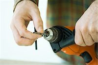 Man adjusting drill bit, cropped view of hands Stock Photo - Premium Royalty-Freenull, Code: 695-05779194