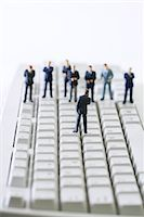 Miniature businessman addressing group of colleagues on computer keyboard Stock Photo - Premium Royalty-Freenull, Code: 695-05779549