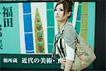 Young female walking past large poster with Japanese script, side view Stock Photo - Premium Royalty-Freenull, Code: 695-05779625