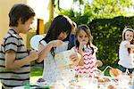 Girl opening gift at birthday party as friends watch Stock Photo - Premium Royalty-Freenull, Code: 695-05779971