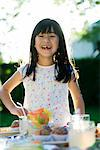 Girl at party admiring sweets placed on table Stock Photo - Premium Royalty-Free, Artist: Aurora Photos, Code: 695-05779993