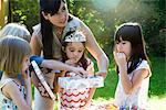 Mother helping daughter open gift at birthday party Stock Photo - Premium Royalty-Freenull, Code: 695-05779999