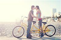 Couple kissing on tandem bike on beach boardwalk Stock Photo - Premium Royalty-Freenull, Code: 6106-05787390
