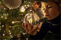 Boy decorating Christmas tree with baubles at home Stock Photo - Premium Royalty-Freenull, Code: 614-05792381