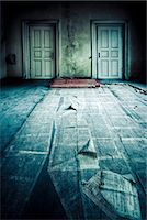 Abandoned room with two doors and newspaper on floor Stock Photo - Premium Royalty-Freenull, Code: 614-05792468