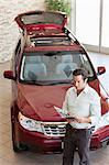 Mid-adult man reading document in front of luxury car in show room Stock Photo - Premium Royalty-Free, Artist: Cusp and Flirt, Code: 693-05793977