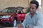 Man signing papers with car in background Stock Photo - Premium Royalty-Free, Artist: CulturaRM, Code: 693-05793981