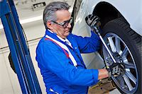 Car mechanic working on car tire Stock Photo - Premium Royalty-Freenull, Code: 693-05794035