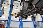 Low angle view of mechanic working under car Stock Photo - Premium Royalty-Free, Artist: Aurora Photos, Code: 693-05794044