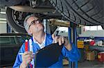 Mechanic analyzing car engine at auto repair shop Stock Photo - Premium Royalty-Free, Artist: Cusp and Flirt, Code: 693-05794051