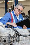 Senior mechanic analyzing car engine and holding clipboard Stock Photo - Premium Royalty-Free, Artist: Blend Images, Code: 693-05794053