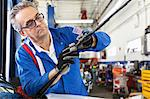 Mechanic working on windshield wipers of car Stock Photo - Premium Royalty-Free, Artist: Blend Images, Code: 693-05794057
