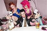 Man holding two playing cards with erotic females sitting besides him Stock Photo - Premium Royalty-Free, Artist: Glowimages, Code: 693-05794163