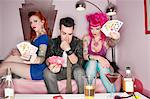 Portrait of females showing their playing cards while man thinking Stock Photo - Premium Royalty-Free, Artist: Sarah Murray, Code: 693-05794169