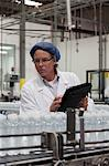 Man at bottling plant inspecting bottled water on conveyor Stock Photo - Premium Royalty-Freenull, Code: 693-05794210