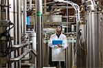 Factory worker inspecting bottling factory Stock Photo - Premium Royalty-Free, Artist: Blend Images, Code: 693-05794222