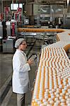 Man inspecting orange juice bottles at bottling plant Stock Photo - Premium Royalty-Freenull, Code: 693-05794228