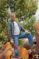 forestry - Lumberjack with an axe standing with stack of chopped firewood in background Stock Photo - Premium Royalty-Freenull, Code: 693-05794383