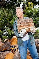 Senior man carrying firewood logs Stock Photo - Premium Royalty-Freenull, Code: 693-05794385