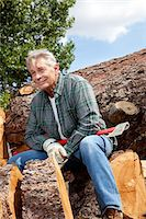 Senior man sitting on wood logs with an axe Stock Photo - Premium Royalty-Freenull, Code: 693-05794388