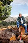 Man sitting on chopped tree trunk Stock Photo - Premium Royalty-Free, Artist: Ron Fehling, Code: 693-05794392