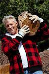 Senior man carrying firewood over his shoulders Stock Photo - Premium Royalty-Freenull, Code: 693-05794400