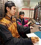 Young Chinese men dressed in traditional Chinese costumes, working as pharmacists selling herbal medicine, Beijing, China, Asia Stock Photo - Premium Rights-Managed, Artist: Robert Harding Images, Code: 841-05796117